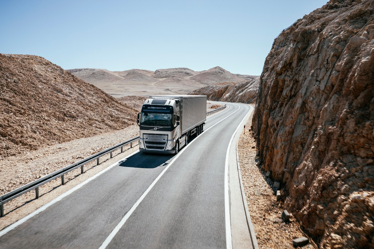 A truck drives through a mountainous desert landscape