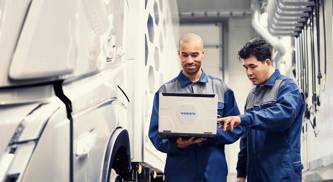 站在貨車旁的兩名 Volvo 服務技師注視著筆記型電腦