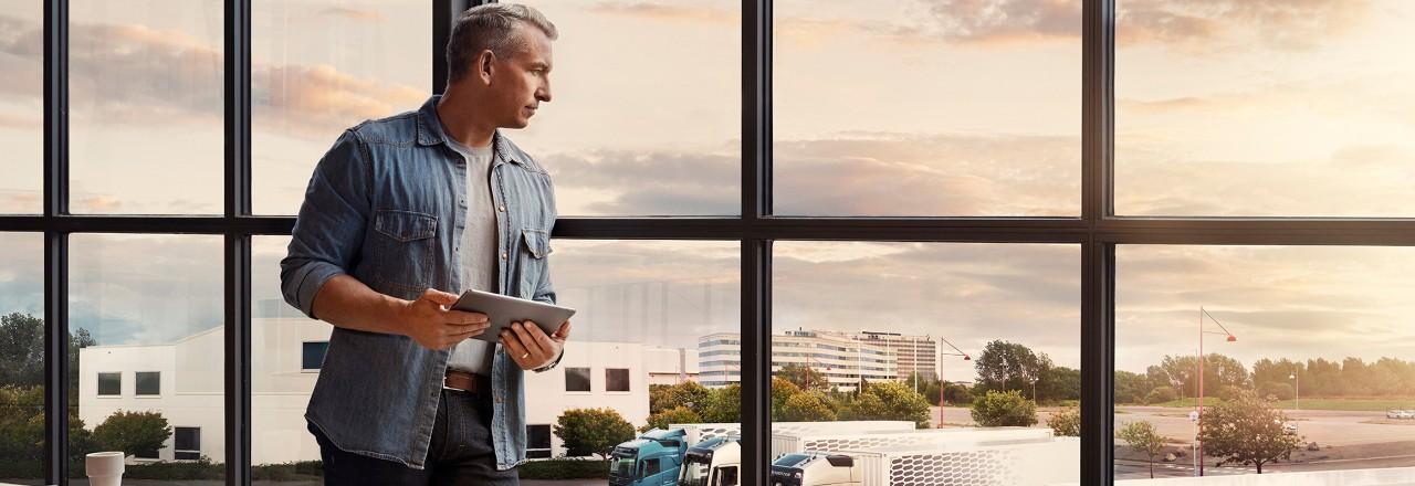 一個人拿著平板電腦站在窗邊,俯瞰他的貨車車隊