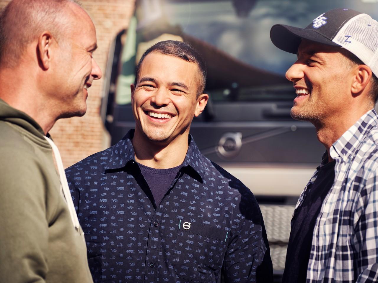 在 Volvo 貨車前微笑的三個男人的特寫畫面