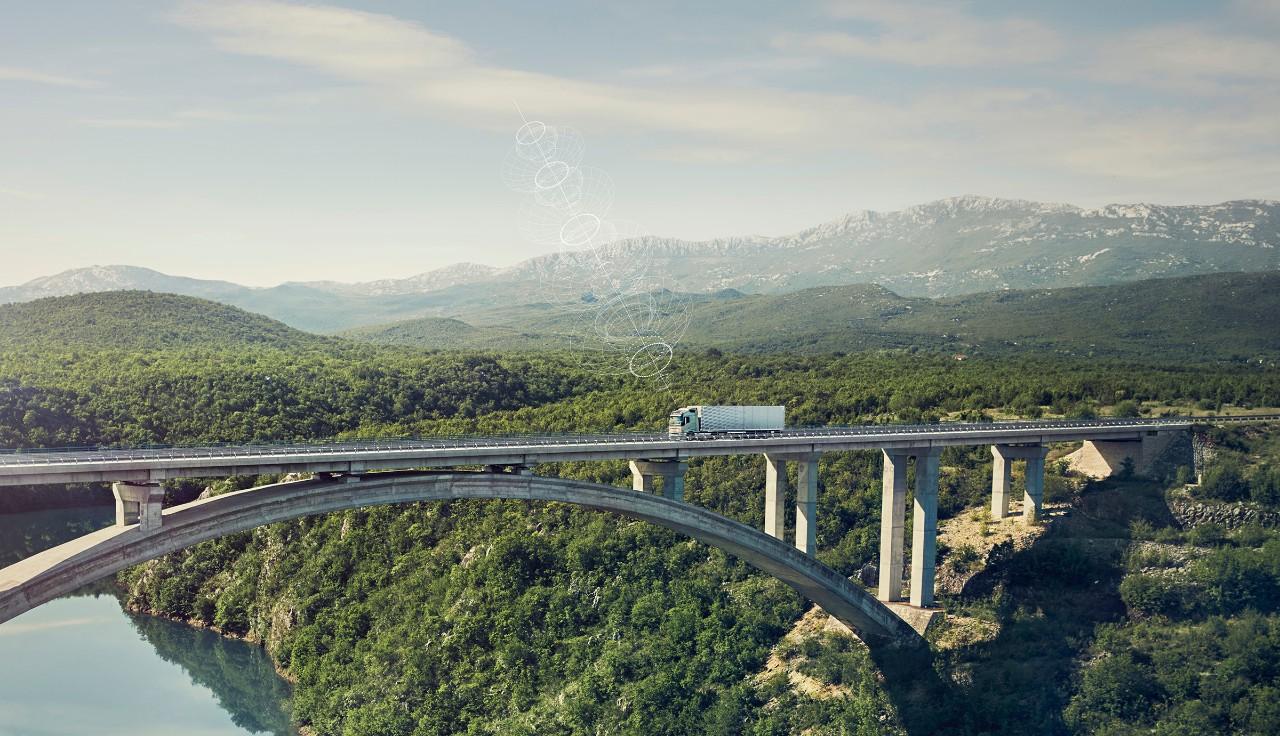 連線的 Volvo 貨車行駛在偏遠地區的橋上